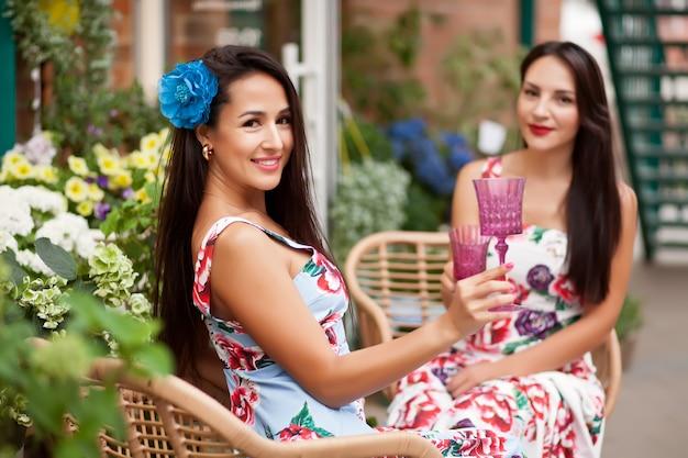 Jovens mulheres morenas lindas em vestidos coloridos, sentado em um café e segurando um óculos com vinho