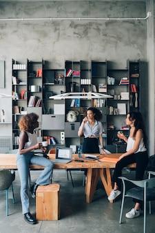 Jovens mulheres multirraciais que têm a reunião informal no escritório moderno do co-working