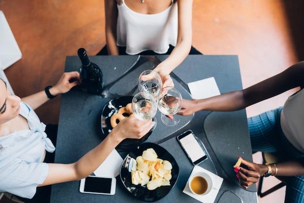 Jovens mulheres multirraciais sentado interior e beber juntos