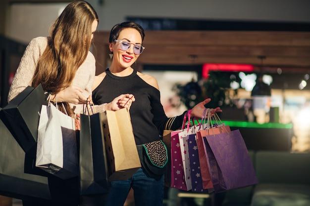 Jovens mulheres olhando para sacolas de compras após a visita no shopping