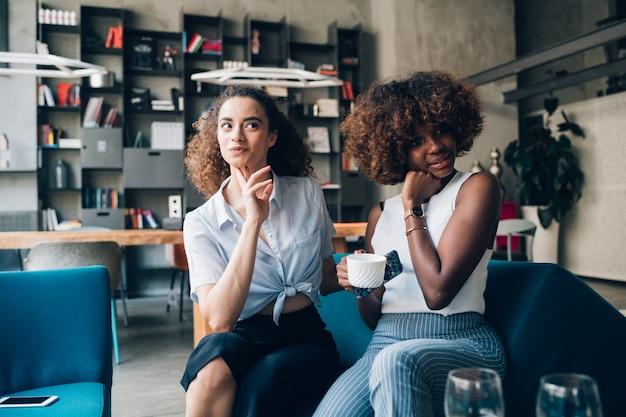 Jovens mulheres posando juntos e tomando café no bistrô moderno