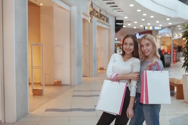 Jovens mulheres que apreciam fazer compras juntos no shopping