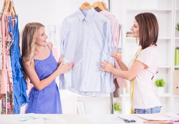 Jovens mulheres que escolhem a roupa em uma cremalheira em uma sala de exposições.