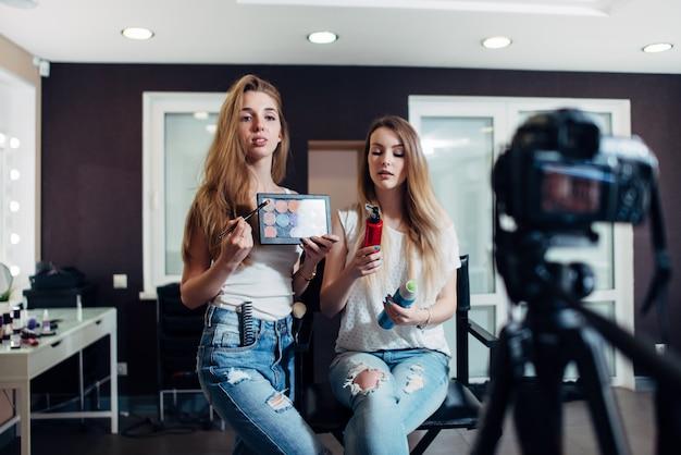 Jovens mulheres segurando produtos de beleza, fazendo um vídeo em cosméticos para videoblog.