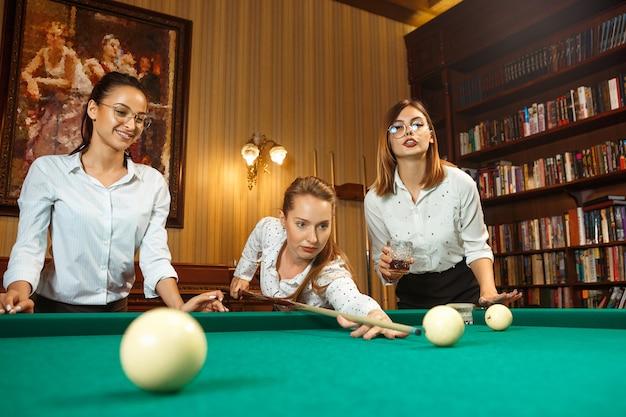 Jovens mulheres sorridentes jogando bilhar no escritório ou em casa depois do trabalho. colegas de trabalho envolvidos em atividades recreativas. amizade, atividade de lazer, conceito de jogo.