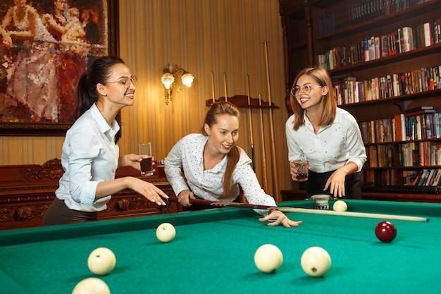 Jovens mulheres sorridentes jogando bilhar no escritório ou em casa depois do trabalho.