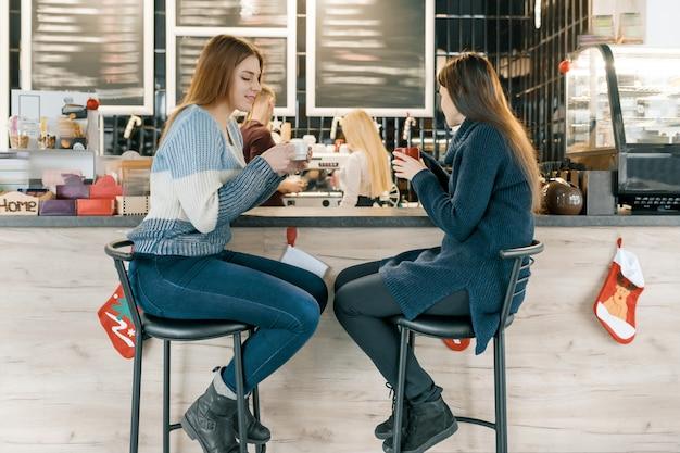 Jovens mulheres tomando café no café, meninas, sentado perto do balcão de bar
