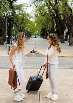 Jovens mulheres trocando o passaporte de visto em pé no parque