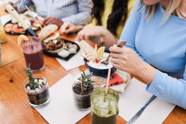 Jovens multirraciais comendo brunch e bebendo smoothies no bar restaurante - foco na mão direita da garota