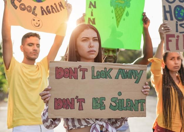 Jovens multirraciais manifestam-se nas ruas com banner pelas mudanças climáticas