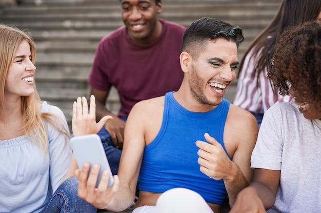 Jovens multirraciais se divertindo na cidade. conceito de amizade e pessoas diferentes - concentre-se no homem transgênero segurando o telefone celular