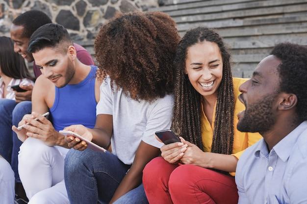 Jovens multirraciais se divertindo na cidade, sentados nas escadas e usando o celular
