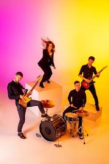Jovens músicos caucasianos, banda se apresentando em luz de néon no fundo gradiente do estúdio