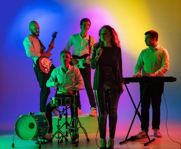 Jovens músicos caucasianos, banda tocando, tocando no espaço gradiente na luz de neon. conceito de música, passatempo, festival