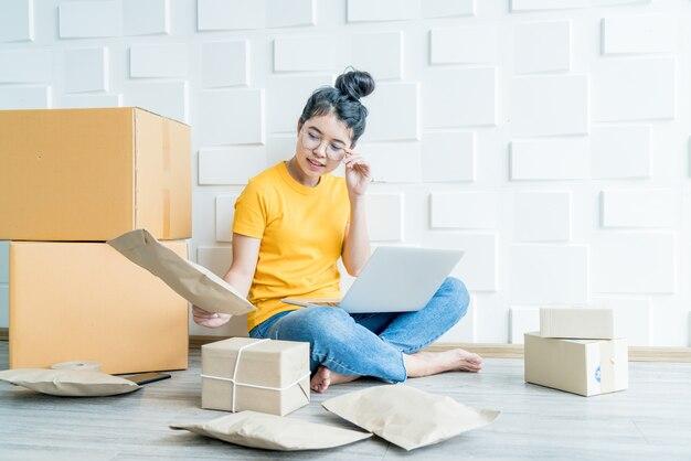 Jovens negócios asiáticos iniciam o proprietário do vendedor on-line usando o computador para verificar os pedidos dos clientes por email ou site e preparar pacotes