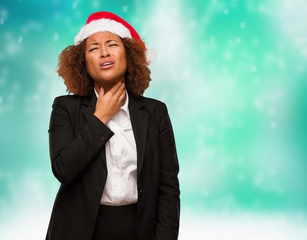 Jovens negócios mulher negra vestindo um chapéu de papai noel chirstmas tosse, doente devido a um vírus ou infecção