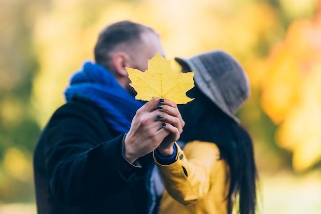 Jovens no parque outono. folhas e árvores amarelas. conceito de família jovem feliz.
