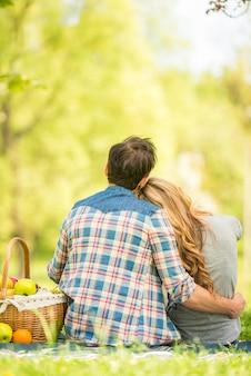Jovens no piquenique romântico no parque de verão.
