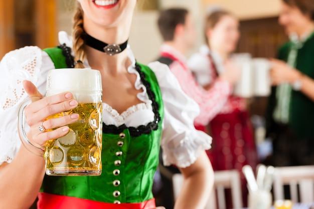 Jovens no tracht tradicional da baviera no restaurante ou pub