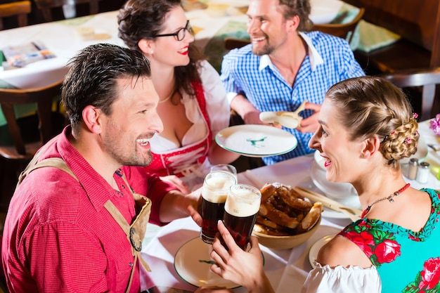 Jovens no tradicional tracht da baviera comendo com salsichas em um restaurante ou pub no almoço ou no jantar