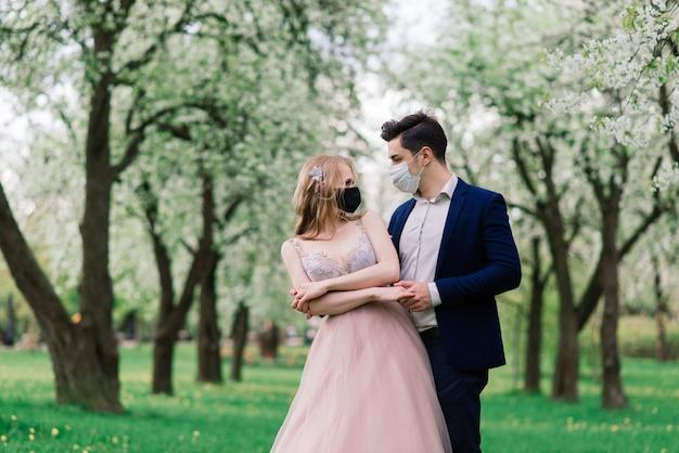 Jovens noivas amorosas no parque com máscaras médicas durante a quarentena no dia do casamento