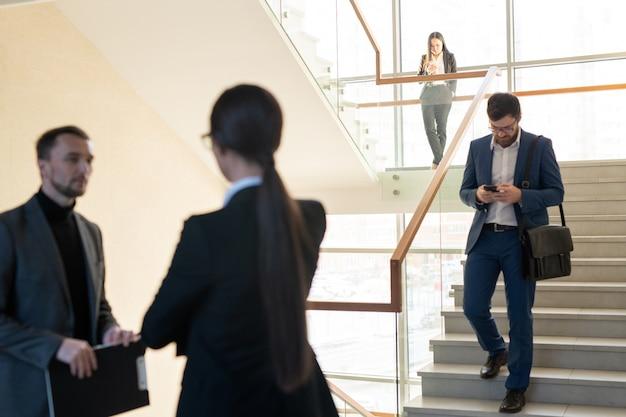 Jovens ocupados movendo-se na escada: homem barbudo verificando o telefone enquanto está em movimento