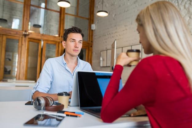 Jovens ocupados sentados à mesa frente a frente, trabalhando em um laptop em um escritório colaborativo