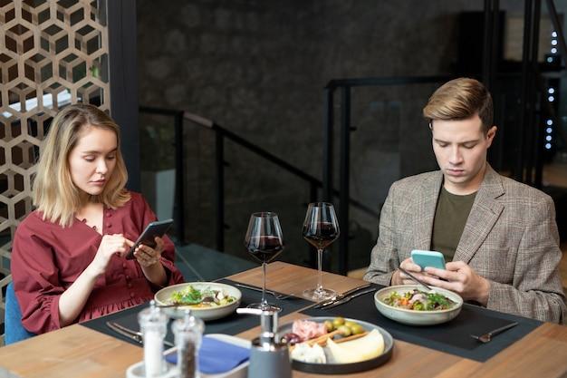 Jovens ofendidos em trajes casuais elegantes expressando indiferença ao usar smartphones na mesa servida durante o jantar no restaurante