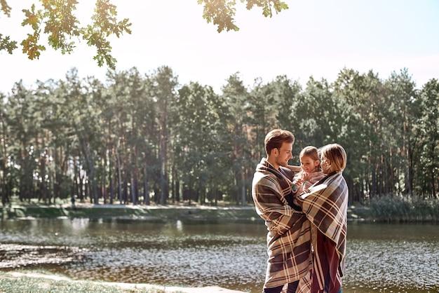 Jovens pais abraçam sua filha na floresta de outono perto do lago.