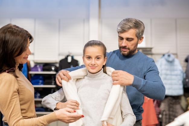 Jovens pais ajudando sua filha a experimentar um novo colete quentinho no departamento de roupas casuais durante as compras sazonais