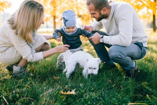 Jovens pais brincando com seu filho no parque outono.
