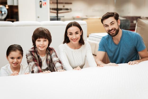 Jovens pais com crianças fofos escolhendo colchão