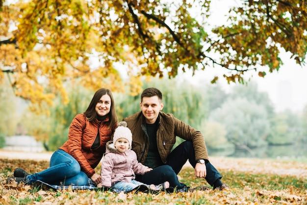 Jovens pais com filha descansando na floresta de outono