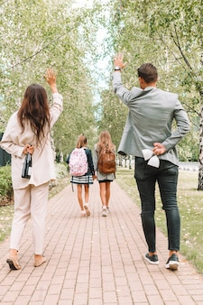 Jovens pais com seus filhos na escola no outono. os pais estão felizes porque os filhos finalmente vão para a escola. de volta à escola