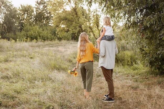 Jovens pais com sua filha caminham na natureza no início do outono. proteção dos pais. final de semana