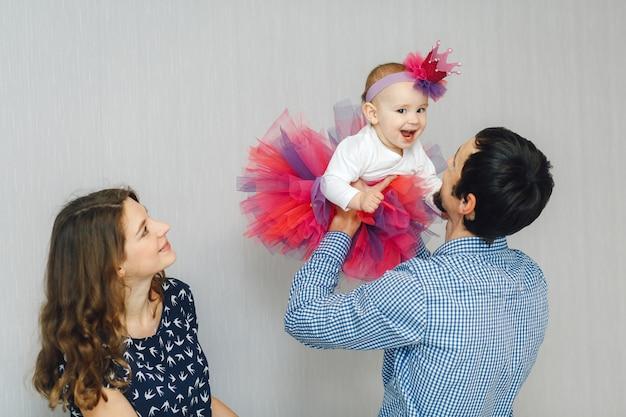 Jovens pais com sua linda filhinha em roupas de férias brilhantes e coroa artesanal