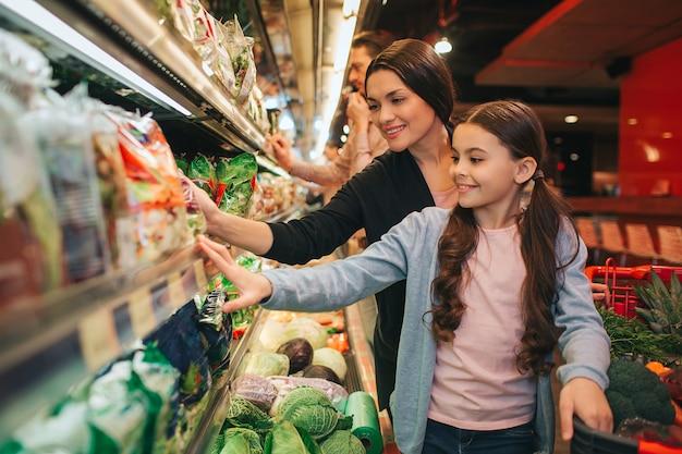 Jovens pais e filha na mercearia. criança e mulher positiva pegar salada juntos. pai fique para trás.