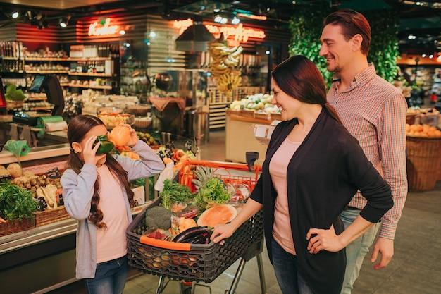 Jovens pais e filha na mercearia. filha brincar com pimentão. ela cobre os olhos com eles. os jovens pais olham para a filha e sorriem.