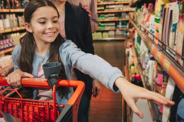 Jovens pais e filha na mercearia. menina pequena chegar à prateleira e sorrir. os pais estão atrás. menina carrega carrinho.