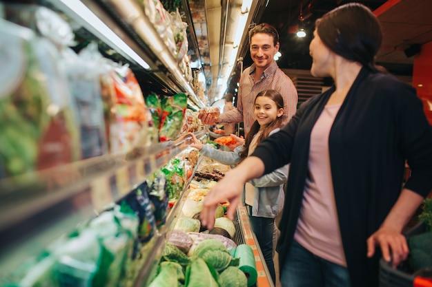 Jovens pais e filha na mercearia. mulher olha para trás e aponta para baixo. pai e filha olham para ela.