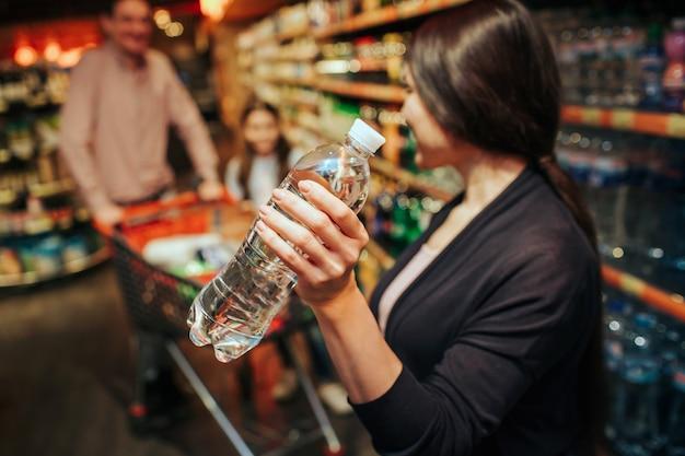 Jovens pais e filha na mercearia. mulher segura a garrafa de água e olha para a família dela. pai e filha estão no carrinho de compras.