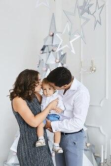 Jovens pais e filho pequeno comemorando o ano novo e os feriados de natal. mulher jovem e bonito, posando com seu filho pequeno bonito no interior decorado para o natal.