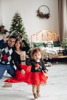 Jovens pais e sua adorável filha passando o natal juntos