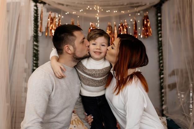 Jovens pais estão beijando seu filho