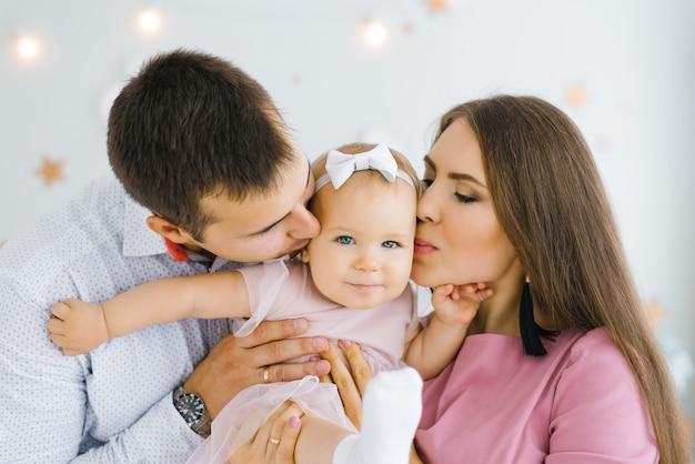 Jovens pais felizes seguram sua filha de um ano nos braços e a beijam na bochecha