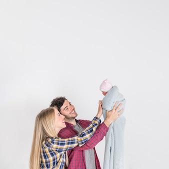 Jovens pais olhando para o bebê nas mãos