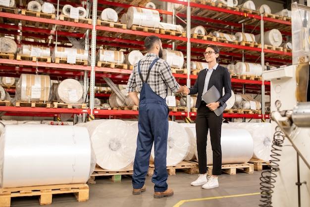 Jovens parceiros contemporâneos se parabenizando por novo acordo comercial após negociação na fábrica