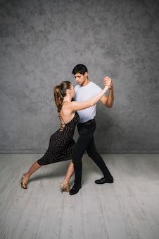 Jovens parceiros de dança dançando tango