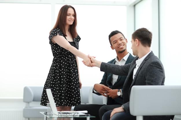 Jovens parceiros de negócios apertando as mãos antes de iniciar uma reunião de negócios