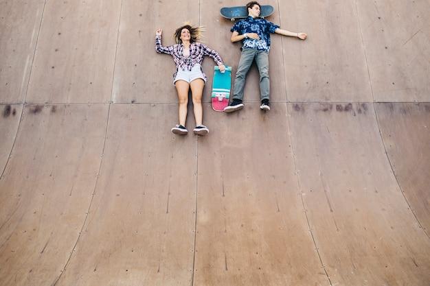 Jovens patinadores que se deitam no halfpipe